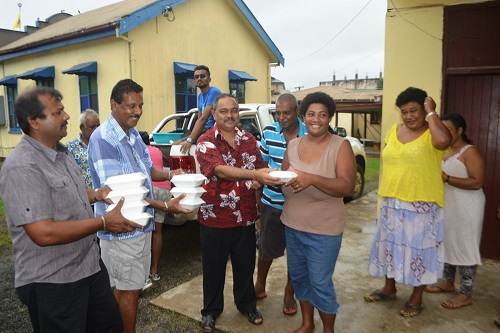 A woman at the Khalsa College evacuation centre in Labasa recieves free food packs from the group's representatives this morning. Picture: LUKE RAWALAI