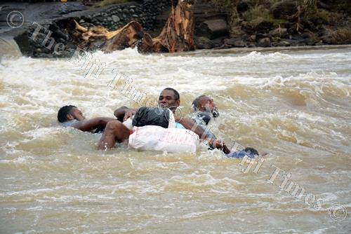 Iona Nailumu rides on a tyre tube with friends as they try to cross a flooded river at Navala Village in Ba. Picture: REINAL CHAND