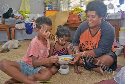 Mereani Nakacia with her daughter Mereula Adi, centre, and granddaughter Asilika Naiuwe tuck into lunch at Lautoka Sangam Primary School evacuation centre yesterday. Picture: BALJEET SINGH