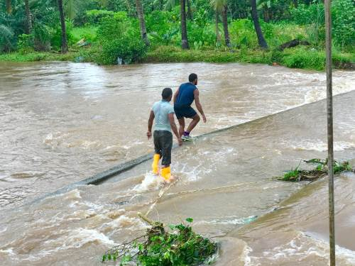 Residents carefully cross the flooded Qauia bridge. Picture: Jovesa Naisua