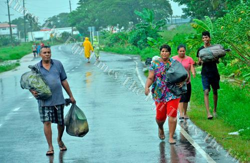 Resident of Korociri settlement in Nadi, Bir Singh, left, with his family members make their way to higher ground during Severe TC Keni yesterday. Picture: BALJEET SINGH