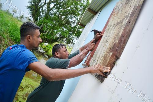 Leaving no stone unturned ... Navua residents Avinsh Raj and Bimlesh Deo put up temporary shutters as they prepared for Tropical Cyclone Keni. Picture: JOVESA NAISUA