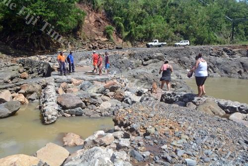 People walk across the severely damaged Nasivi Irish crossing in Vatukoula. Picture: REINAL CHAND