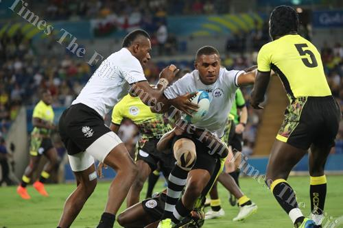 Fiji 7s forward Jasa Veremalua tries to fend off Uganda players during the Commonwealth Games 7s tournament at the Robina Stadium, Gold Coast in Australia yesterday. The semi-final beings at 1.43pm today. The men 7s gold medal final is scheduled for 5.04p