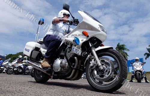 A police officer rides a motorbike during the handing over ceremony at the ANZ Stadium carpark yesterday. Picture: ATU RASEA